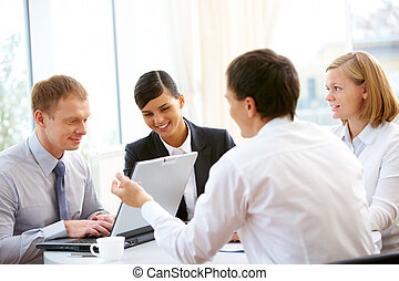 Business team - Business people sitting around the table and...