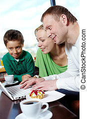 Surfing internet at cafe - Family of three spending time at...