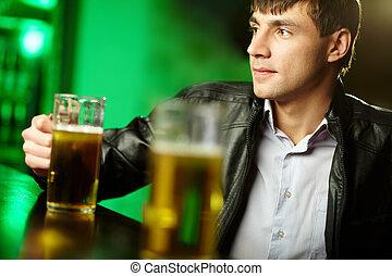 Guy at bar counter - Young man sitting at bar counter with a...