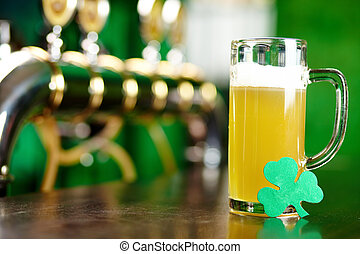 Beer pint - A glass of beer on a bar counter with a leaf of...