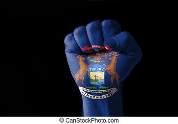 Fist painted in colors of us state of michigan flag