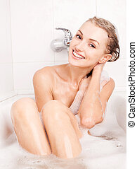 woman taking a bath - beautiful young blond woman taking a...