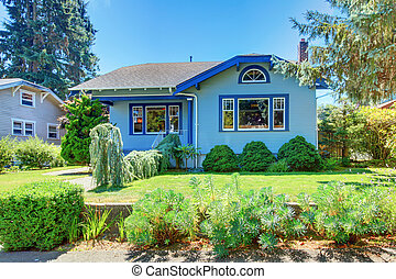 Blue old cute house with front green yard.