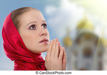 beautiful young woman in a scarf prays to God