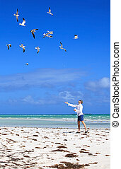 Man on the beach feeding sea gulls.