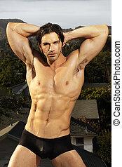 Bodybuilder posing - Beautiful muscular male model in black...