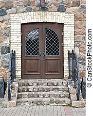 Front door of a old mansion with decorative metal handrail