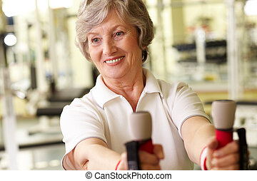 Senior lady at gym - Tilt up of a pretty mature lady working...