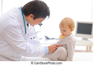 Baby on examination being checked by pediatric doctor