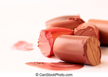 Multi-coloured scraps of lipstick on a white background for...