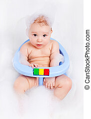 baby taking a bath - cute six months old baby sitting in the...