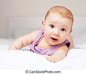 baby on the bed - cute six months old baby on the bed at...