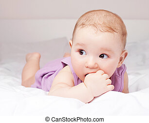 baby in bed - cute six months old baby lies in the bed at...