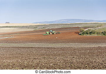 Tractor with drill seed working in an arable field, Ciudad...