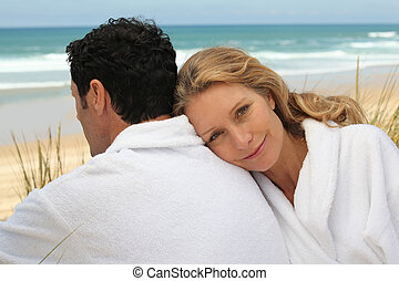 A man and a woman wearing dressing gowns on a beach.