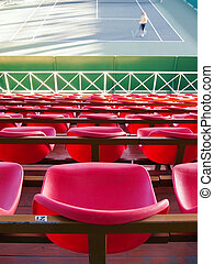 Empty tribune with red seats over tennis court