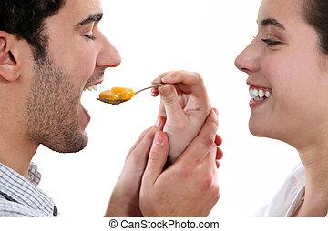 A woman feeding her man.
