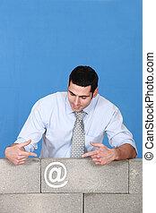 Man pointing towards at symbol stuck to wall