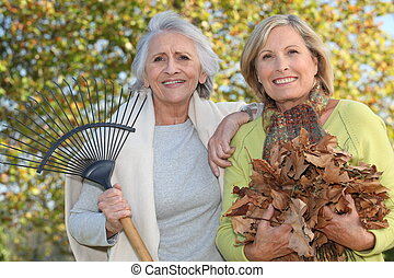 Mother and daughter collecting leaves