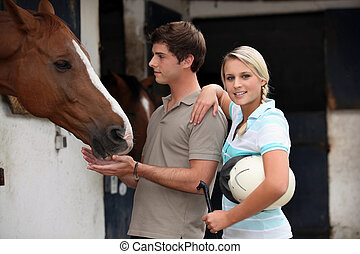 Young couple at a stable