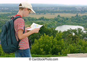 Boy with binoculars and backpack looks at the map on a hike...