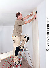 Handyman laying wallpaper