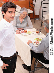 an old couple eating at restaurant and a young waiter