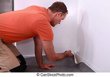 Workman putting down linoleum flooring