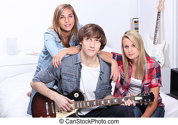 Teenager with guitar sat with friends