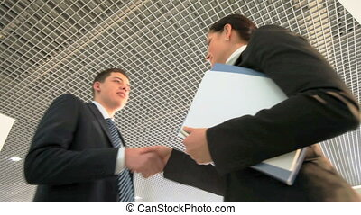 Business acquaintance - Two businesspeople meeting, shaking...