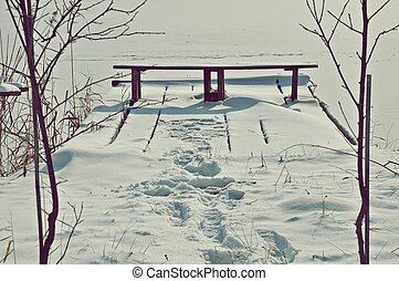 bench at the river in winter
