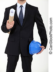 Architect carrying his helmet and a blueprint