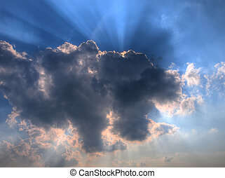Sun rays from behind a summer cloud in hdr