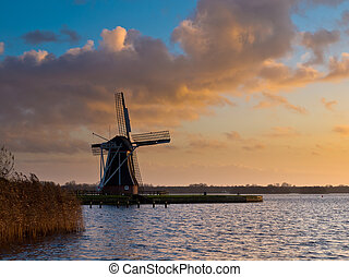 traditional dutch windmill during windy orange sunset