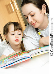 mother and daughter reading a book - young mother and her...