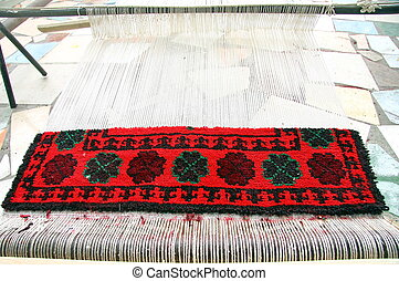 Incomplete Kyrgyz carpet being woven on a loom