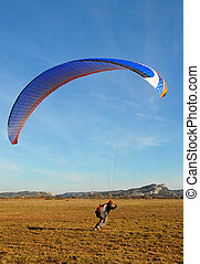 paragliding - a paragliding running in a field for training