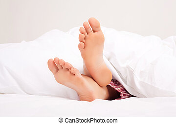 feet of a sleeping woman - feet of a woman sleeping on the...