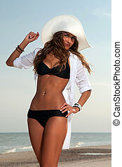 beautiful woman in a bathing suit standing on the beach at...