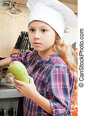 girl in a chef cap helps to make a dinner.