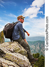 man - tourist sits on a rock and admires a mountain...