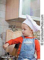 amusing kid in a chef cap on kitchen