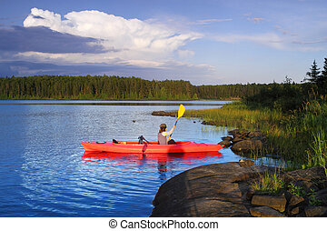 Girl canoeing - Woman canoeing in a beautiful lake at sunset