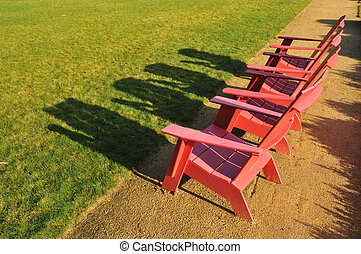Three red adirondack chairs on a path
