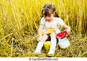 girl eating a long loaf and milk - happy cute little girl in...