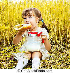 girl eating a long loaf - cute little girl in the wheat...