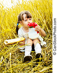 picnic - cute little girl in the wheat field eating a long...