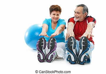 stretching exercise - senior couple doing stretching...