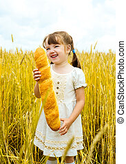 girl with a long loaf - happy cute little girl in the wheat...
