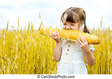 girl eating a long loaf - happy cute little girl in the...